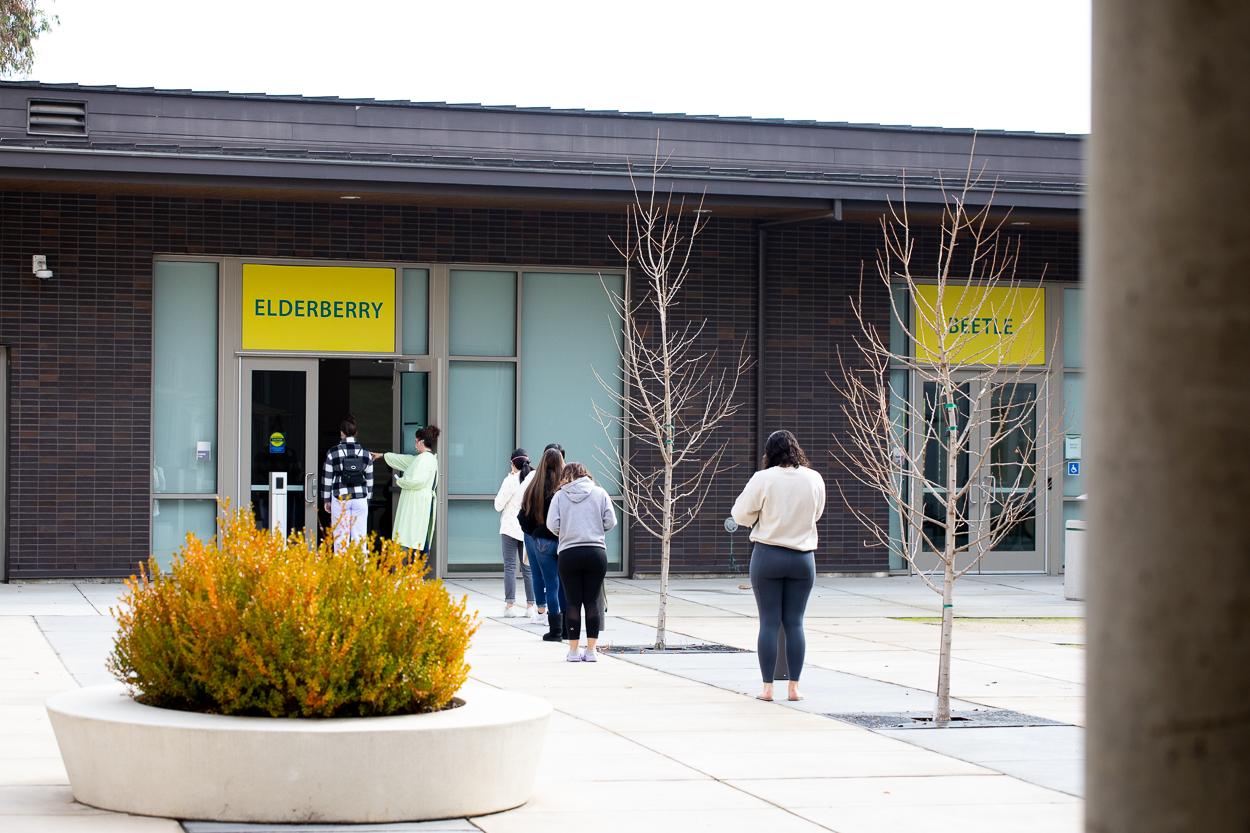students wait in line outside