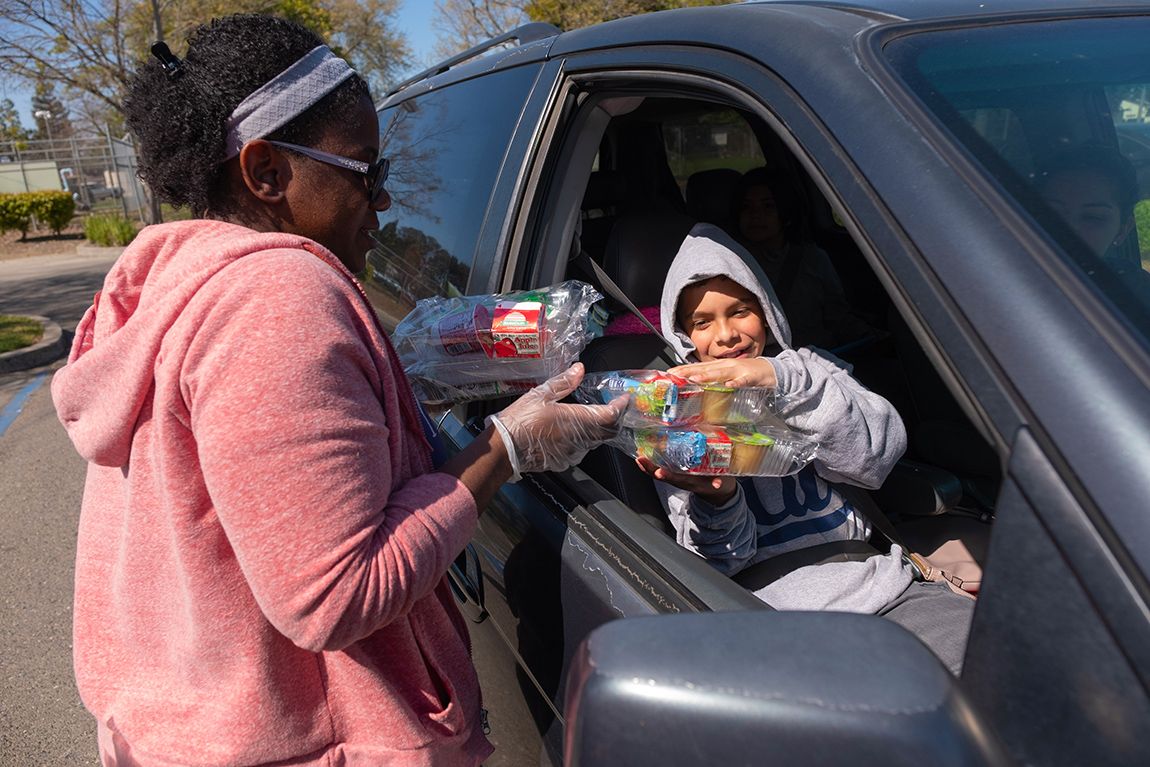 A woman hands a boxed lunch to a student through an open car window.