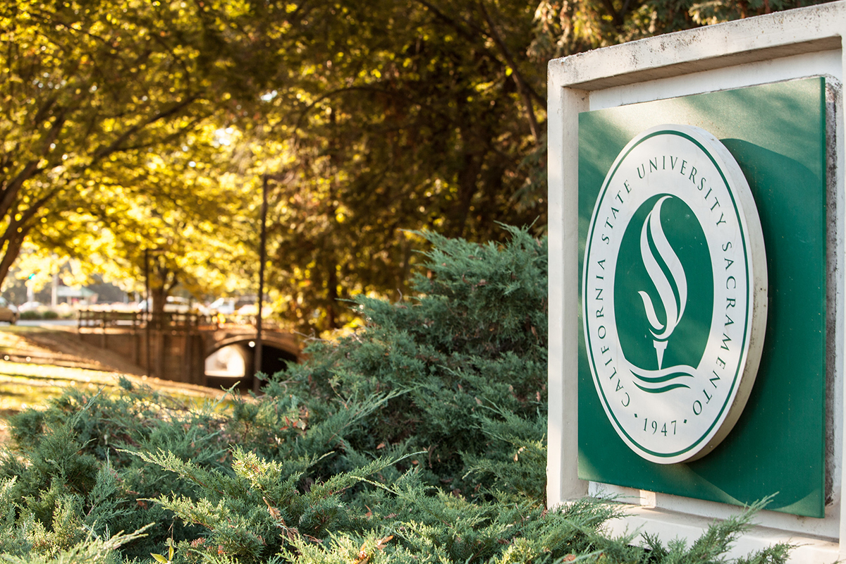A photo of the CSUS sign at the front of campus, with a walkway and trees in the background