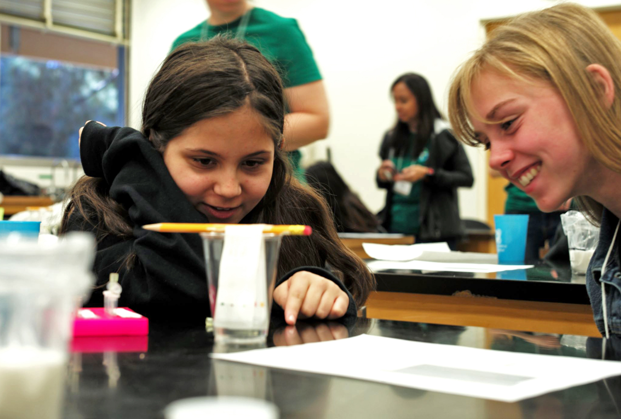 A girl in a science lab looking at a pencil being suspended over a glass cup