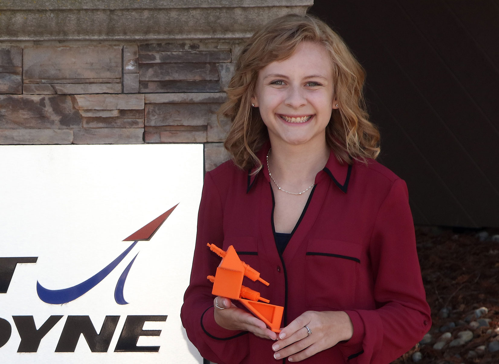 A photo of Sac State student Elizabeth Gabler holding a model of the bracket she designed for Aerojet Rockeydyne
