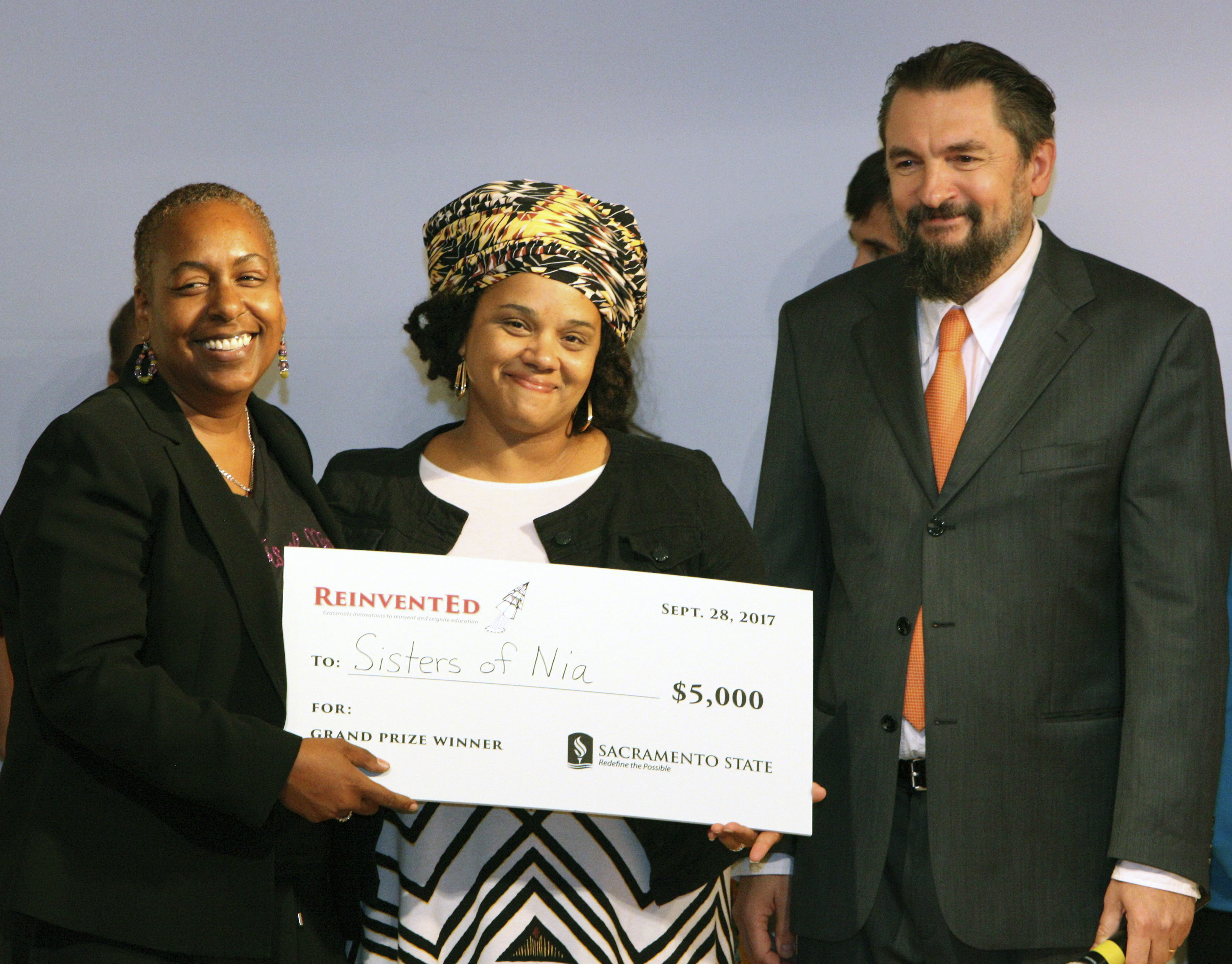 Sisters of Nia co-founders Synthia Smith and Malika Hollinside, holding a $5,000 prize check alongside College of Education Dean Sasha Sidorkin.