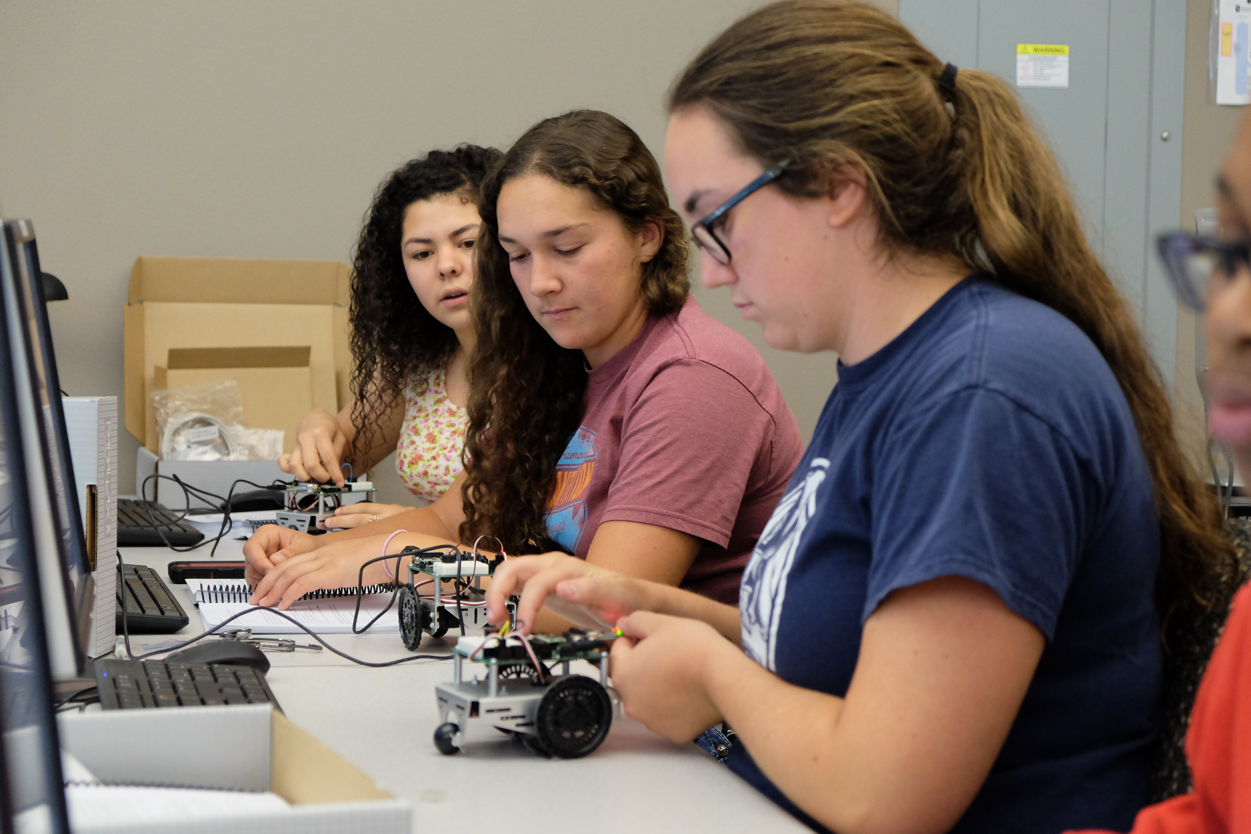 A photo of three high school students at a desk working on small robots.