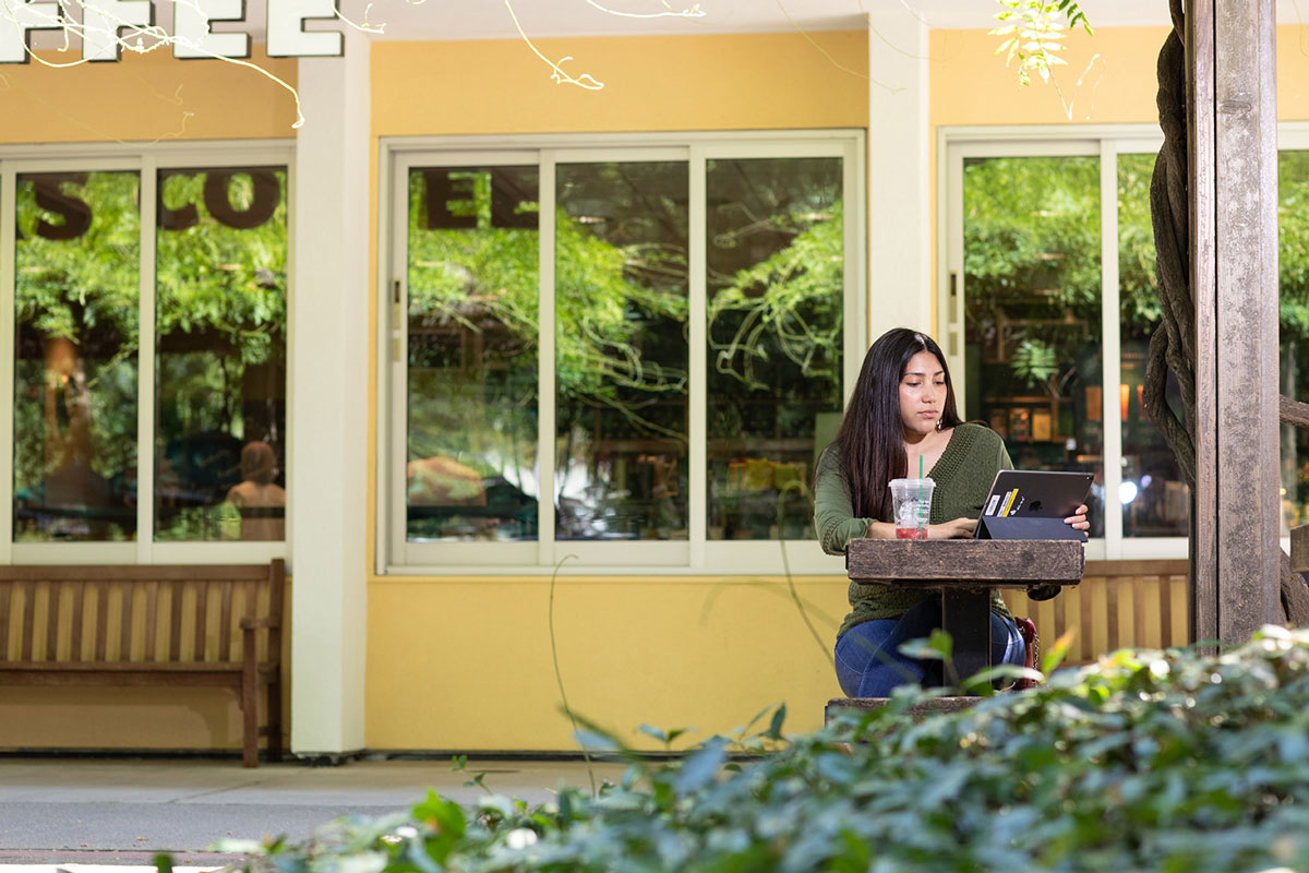 A photo of a student studying outside on an iPad