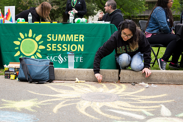 A photo of a student drawing on the pavement with chalk, in front of a table with a green banner reading 'Summer Session'