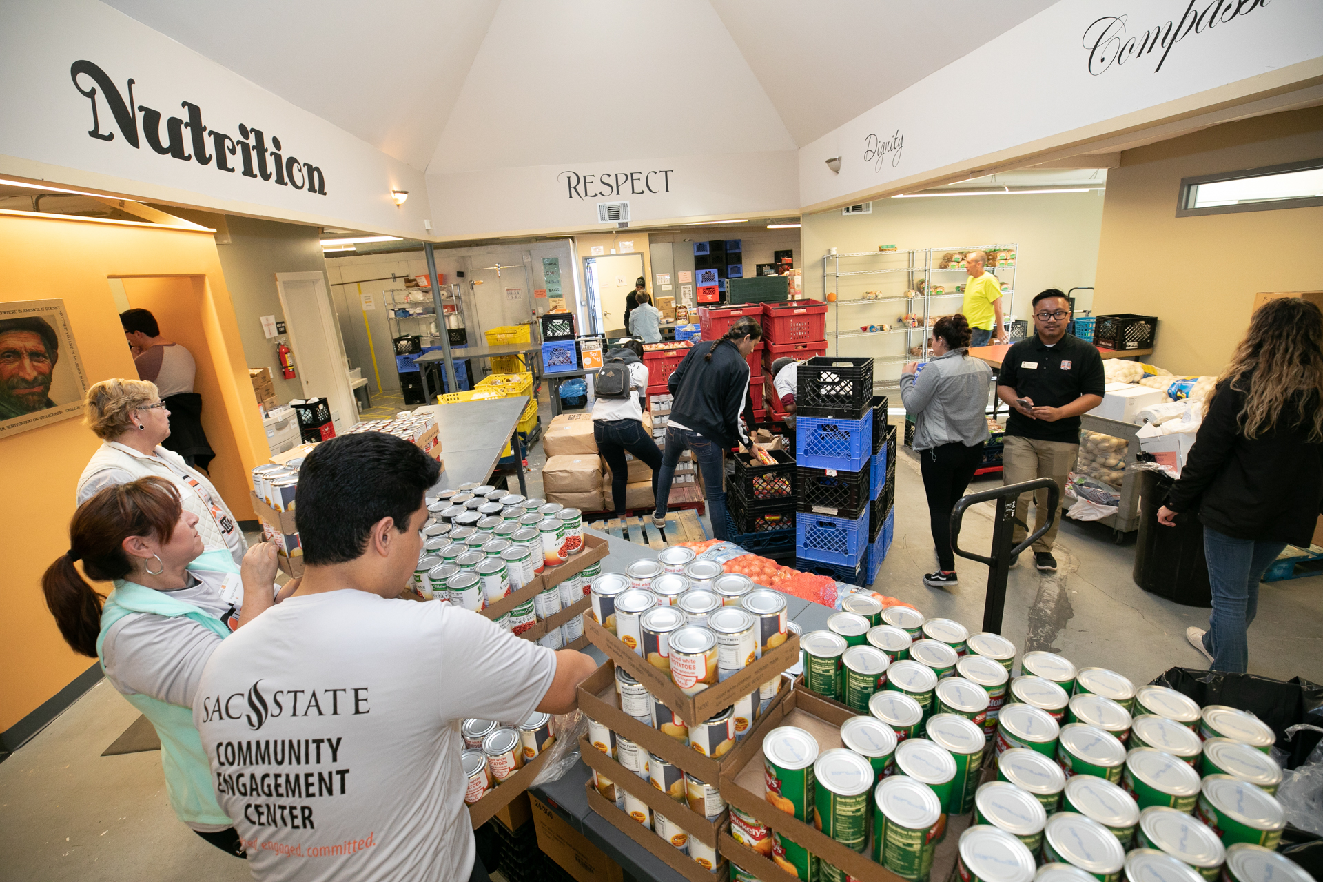 Sacramento State students and River City Food Bank staff distributing canned food and other food items