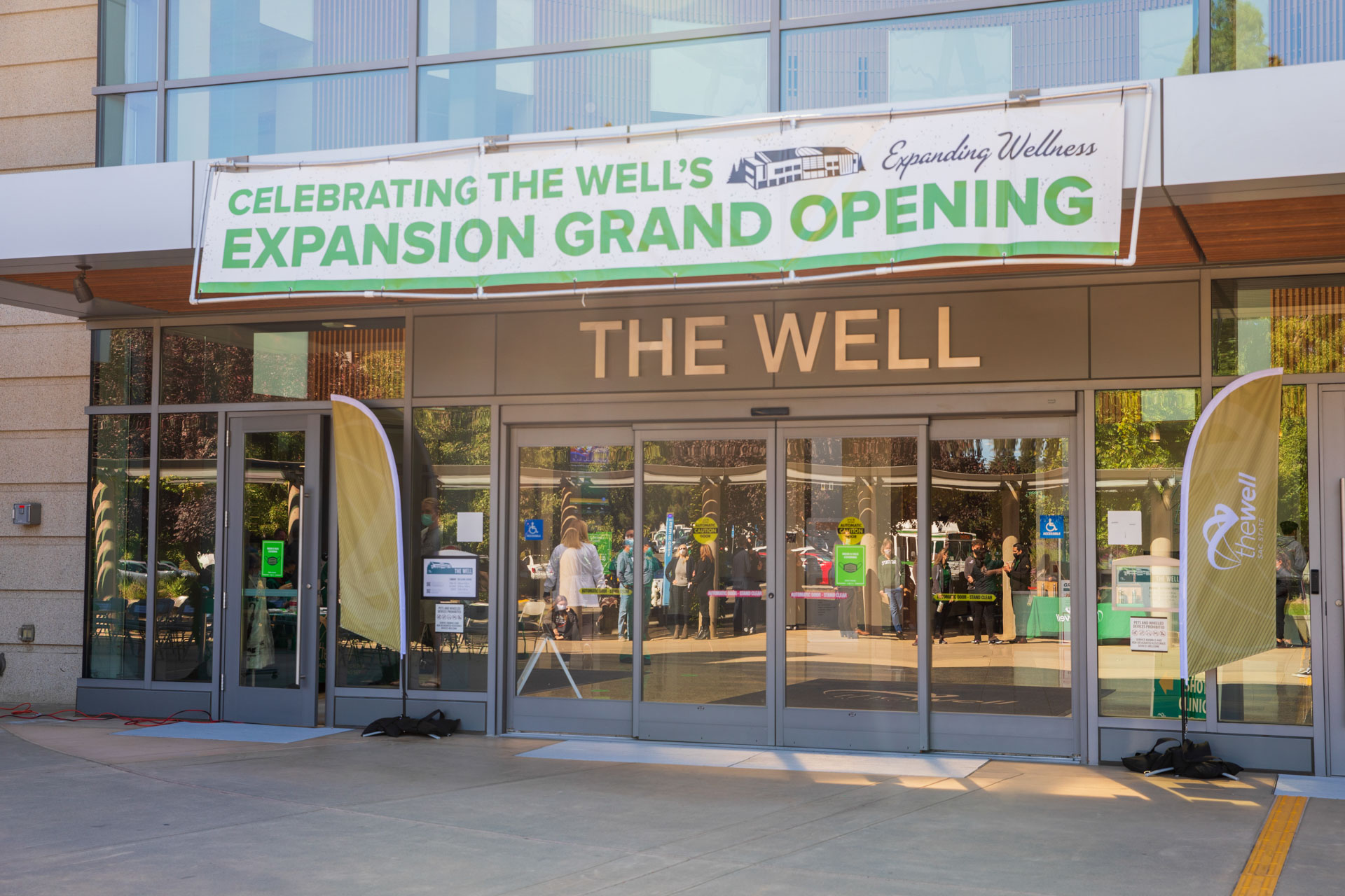 The front entrance of The WELL building, with a banner reading Celebrating The WELL's expansion grand opening above the sliding doors