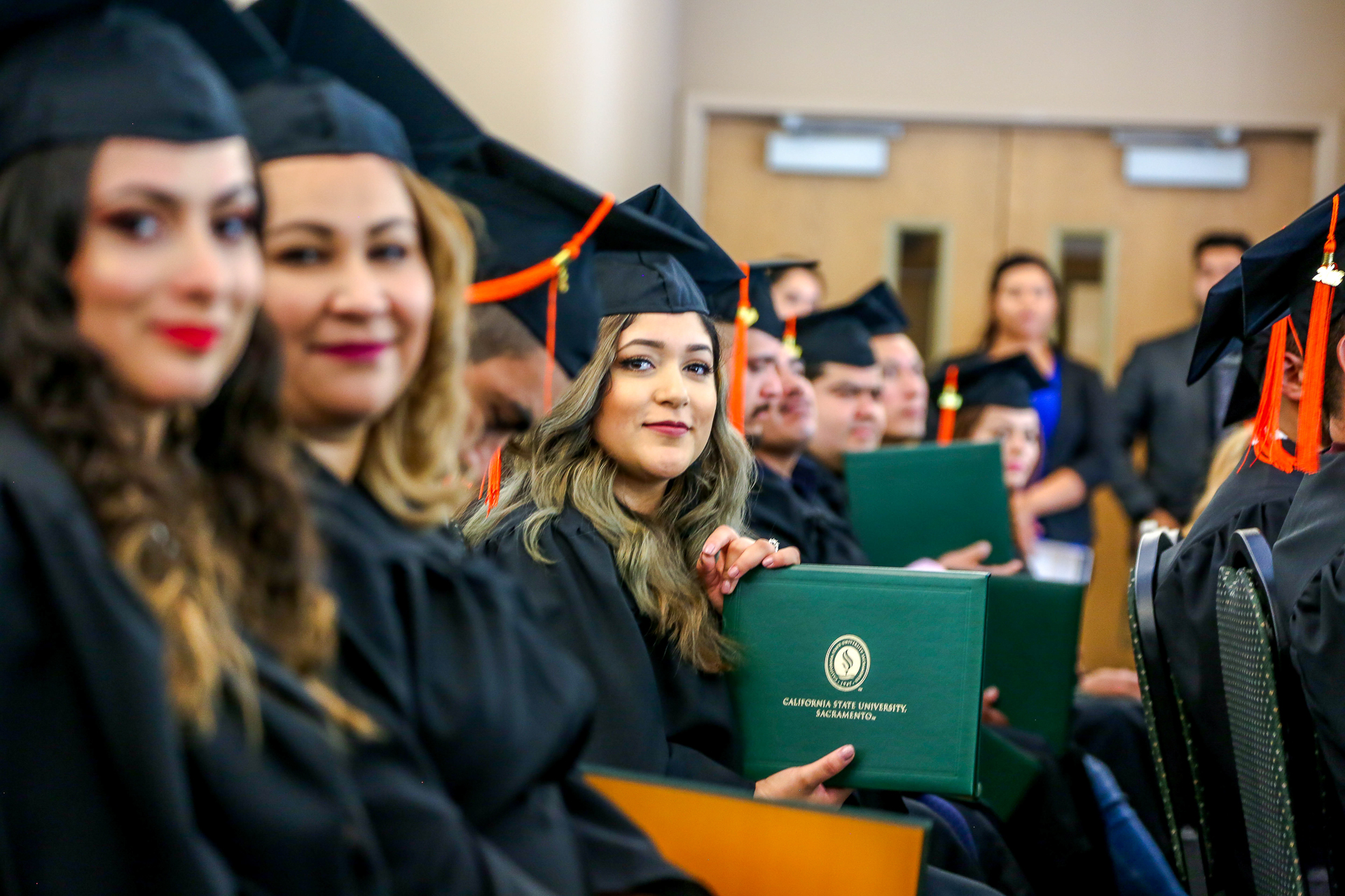 Graduates in caps and gowns, one of whom is holding a green Sac State diploma