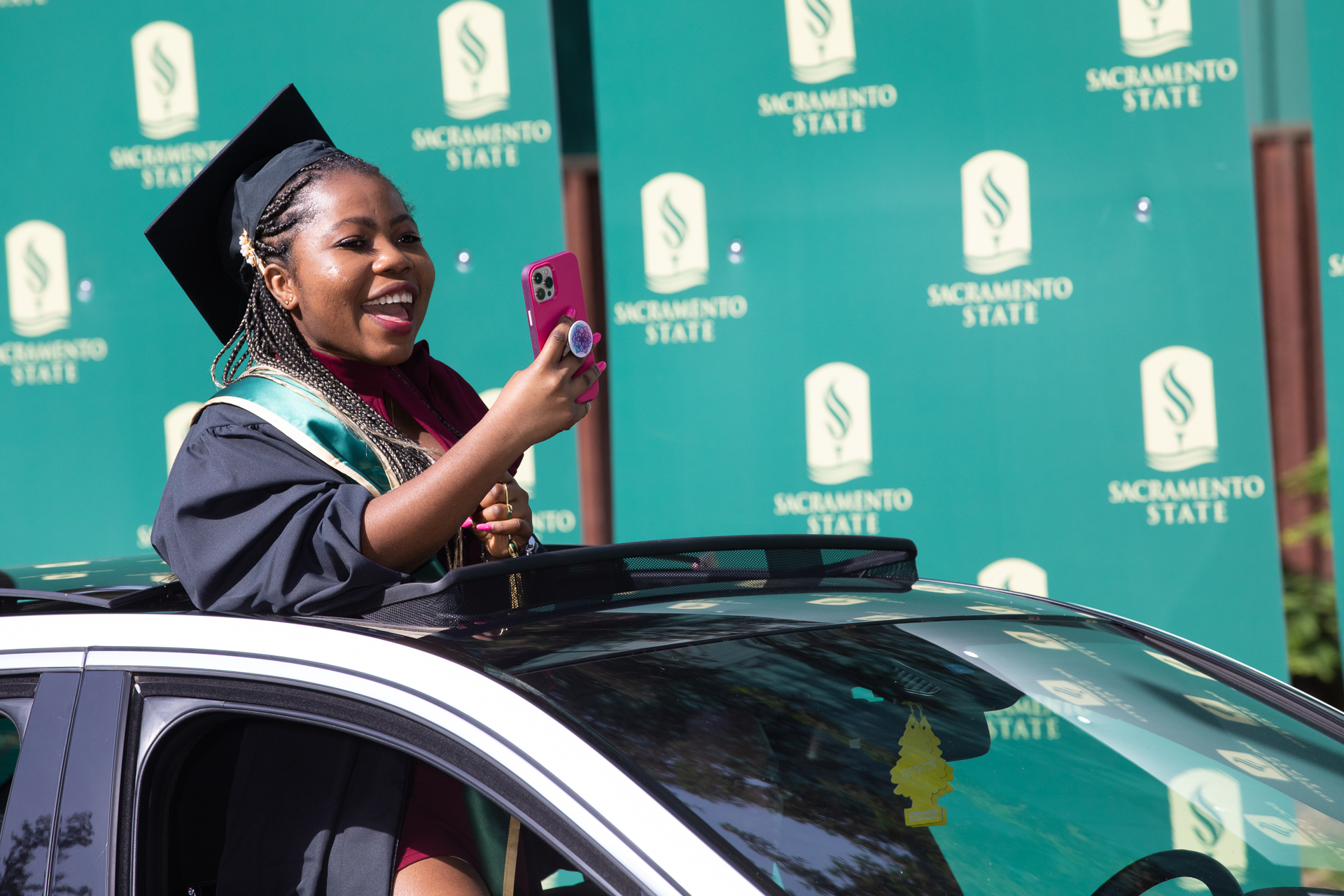 """A Sac State graduate enjoys the experience of the 2021 """"Carmencement"""" ceremony. (Sacramento State/Andrea Price)"""